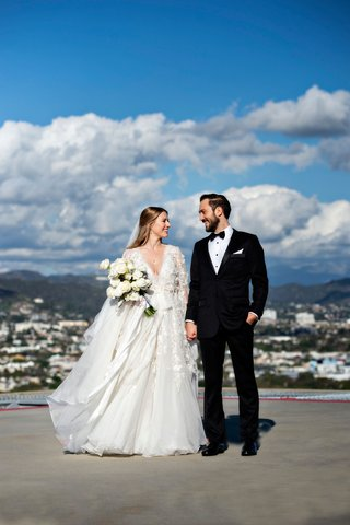 bride-in-marchesa-long-sleeve-wedding-dress-and-groom-in-tuxedo-long-hair-portrait-helipad-rooftop