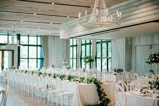 white-wash-wood-room-black-frame-windows-white-decor-chairs-linens-greenery-long-garland-chandelier