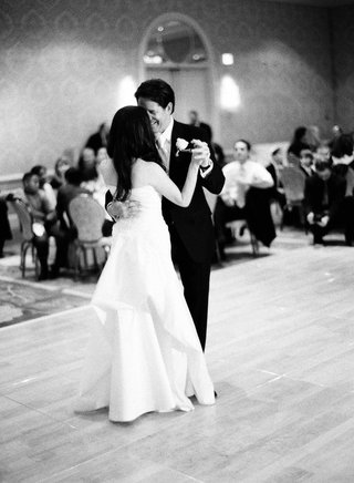 bride-in-a-pronovias-gown-with-a-bustle-train-dances-with-groom-in-black-tuxedo