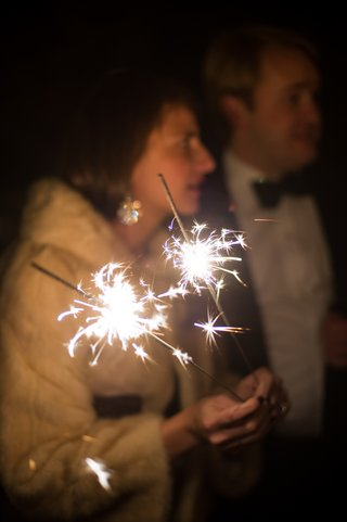 wedding-guest-in-fur-jacket-holds-sparking-sparklers