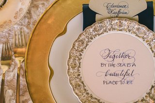 wedding-reception-place-setting-with-gold-china-and-quote-about-the-sea-written-in-calligraphy