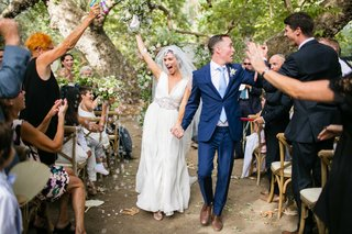bride-in-jenny-packham-wedding-dress-and-groom-in-navy-blue-suit-hold-hands-up-wedding-ceremony