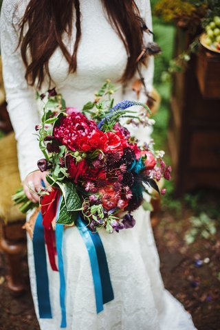 brides-bouquet-of-wildflowers-in-red-purple-blue-colors-and-greenery-wrapped-with-blue-ribbons