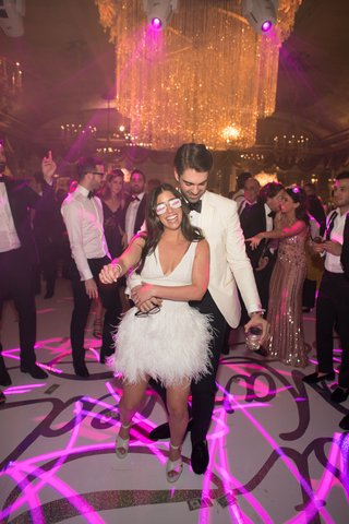 bride-in-v-neck-short-wedding-dress-ostrich-feather-skirt-high-heels-pink-neon-lighting-on-dance