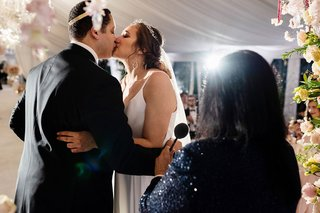 wedding kiss with view of guests lighting streaming in ceremony beverly hills four seasons
