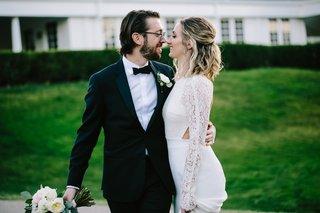 groom-in-tuxedo-holds-brides-bouquet-groom-puts-arm-around-bride-in-sarah-seven-wedding-dress