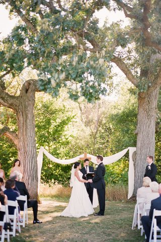 bride-and-groom-at-outdoor-ceremony-between-two-oak-trees-decorated-with-cloth-and-a-cross