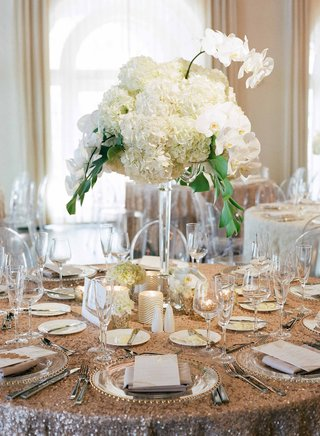 reception-round-table-gold-sequin-linen-tall-centerpiece-greenery-white-hydrangea-white-orchid