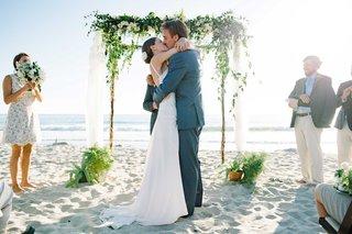 first-kiss-ceremony-beach-pacific-ocean-wood-arch-verdure-sand-oceanside-california-wedding