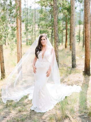 bride-in-pnina-tornai-wedding-dress-with-lace-cutouts-and-inserts-cathedral-veil-in-woods