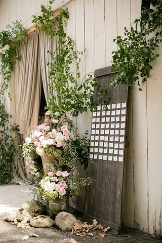 wood-board-in-front-of-barn-with-pink-and-white-flowers-greenery-escort-cards-wedding-reception