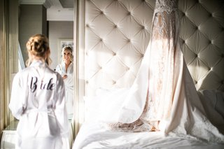 bride in bridal suite at four seasons hotel los angeles at beverly hills bride robe wedding dress hanging on bed headboard