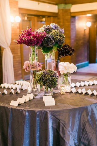 wedding-reception-round-escort-card-table-with-roses-calla-lilies-hydrangeas-and-other-flowers