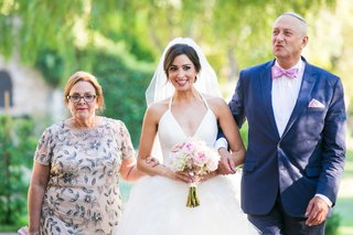 a-bride-in-a-tulle-ball-gown-holding-a-blush-and-ivory-bouquet-walks-down-aisle-escorted-parents