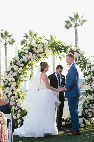 wedding-ceremony-arch-flowers-by-cina-bride-and-groom-with-officiant-ocean-view-palm-trees
