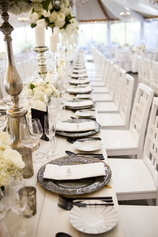 long-reception-table-metallic-chargers-grey-white-florals-roses-greenery-simple-chairs
