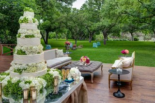 wedding-reception-with-white-wedding-cake-surrounded-by-green-trees-on-a-ranch-in-texas
