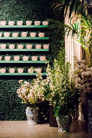 hedge wall of greenery with rainbow sprinkle cookie favors where escort cards used to be