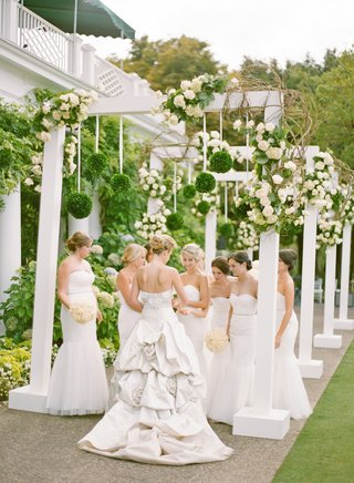 white-bridesmaid-dresses-at-flower-arch-reception
