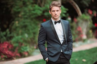 groom-wears-dark-blue-tuxedo-jacket-with-black-pants-and-bow-tie-eden-gardens-ca