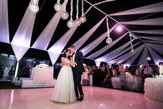 bride-in-wedding-dress-and-groom-in-tuxedo-on-dance-floor-with-overhead-lights-and-drapes-at-rooftop