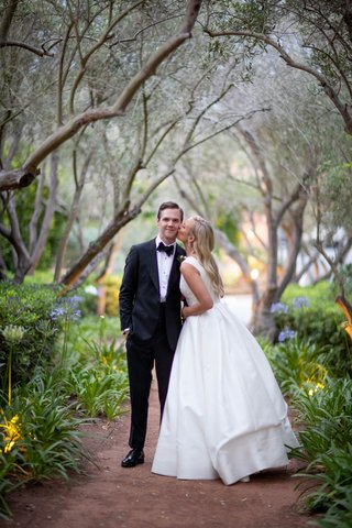 bride with long blonde hair kissing groom on cheek in tuxedo rancho santa fe san diego wedding
