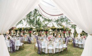 wedding reception long tables greenery overhead round tables purple chair covers colorful flowers