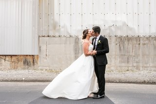 bride-in-modern-trousseau-ball-gown-with-lace-back-spaghetti-straps-and-pockets-kisses-groom