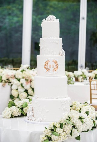 white-wedding-cake-with-sugar-roses-vines-and-couples-monogram-crest-in-gold