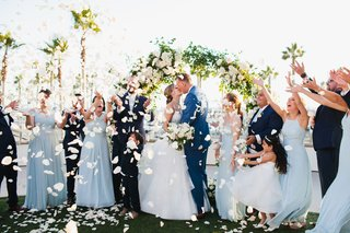 bride-and-groom-kiss-bridesmaids-and-groomsmen-toss-rose-petals-ocean-view-ceremony-palm-trees