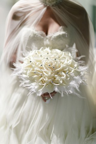 bridal-glamelia-bouquet-dotted-with-crystals-in-bed-of-feathers