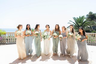 bride-and-seven-bridesmaids-in-mismatched-dresses-in-soft-muted-colors-of-cream-gray-sage-blue