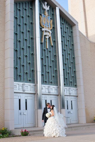 bride-in-ruffle-wedding-dress-kisses-tux-groom-in-front-of-church
