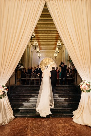 bride-in-wedding-dress-and-veil-walking-up-steps-with-father-of-bride-through-drapery-toward-gold