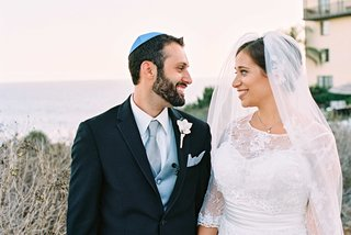 groom-in-dark-suit-with-blue-tie-vest-and-yarmulke-with-bride-in-lace-alfred-angelo-wedding-dress