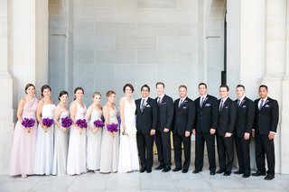 bridesmaids-in-muted-colors-and-vibrant-purple-bouquets