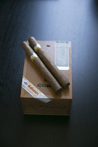 two-cuban-cigars-with-gold-labels-on-box-for-groom