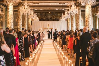 wedding-ceremony-candles-along-aisle-guests-standing-wood-cross-at-altar