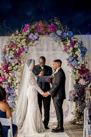 bride-and-groom-exchange-vows-in-front-of-poem-on-backdrop-arch-of-blue-and-purple-flowers