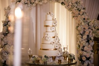 wedding-cake-on-round-table-with-gold-ribbon-details-under-flower-arch-ivory-sugar-flowers