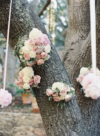 light-pink-and-ivory-rose-pomanders-hanging-from-white-ribbons-on-large-oak-tree-at-ceremony