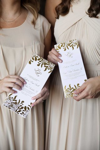attendants-in-champagne-dresses-holding-white-and-gold-foil-ceremony-programs-rectangle-design
