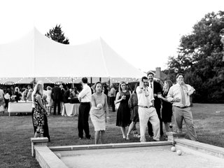 black-and-white-photo-of-guests-playing-bocce-ball-lawn-game-at-outdoor-wedding-tent-reception