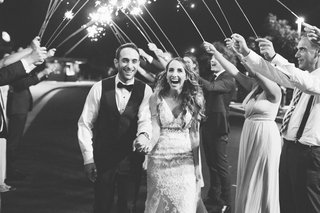 black-and-white-photo-of-groom-in-vest-and-bride-in-lace-gown-during-sparkler-exit