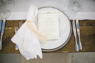 wooden-table-topped-with-white-napkin-and-pink-tie