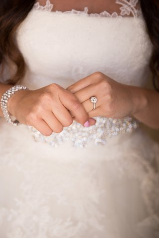 close-up-picture-of-brides-engagement-ring-and-crystal-bracelet