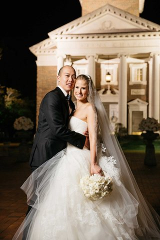 bride-in-vera-wang-strapless-wedding-dress-with-groom-in-front-of-chapel-at-smu
