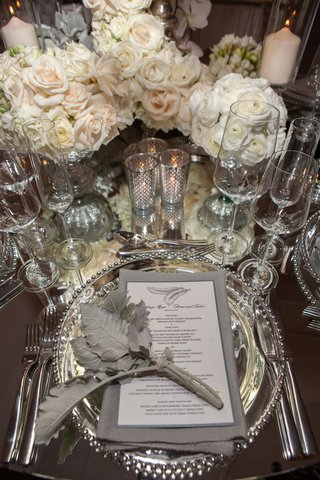 wedding-reception-place-setting-mirror-table-silver-beaded-charger-plate-grey-napkin-feather-decor