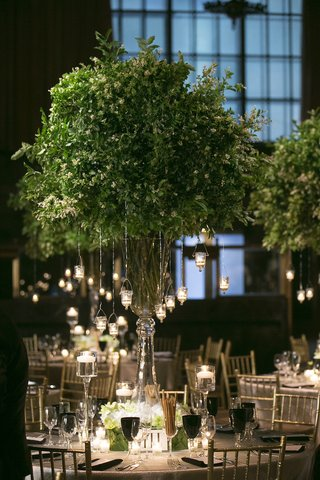 wedding-reception-table-with-tall-vase-filled-with-foliage-branches-suspended-votive-candles