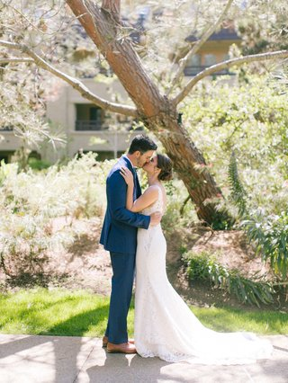 bride-in-wedding-dress-hair-in-low-bun-updo-groom-in-navy-suit-brown-shoes-lodge-at-torrey-pines